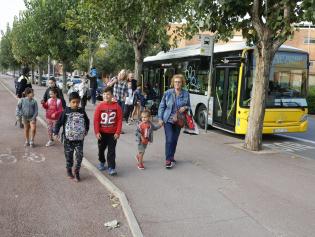 Infants arribant en bus a l'escola
