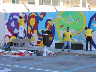 Alumnes de les escoles d'art i disseny pintant la tanca